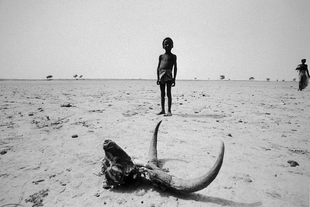 A child from a Mali tribe standing in the Sahara desert during the 1973 famine