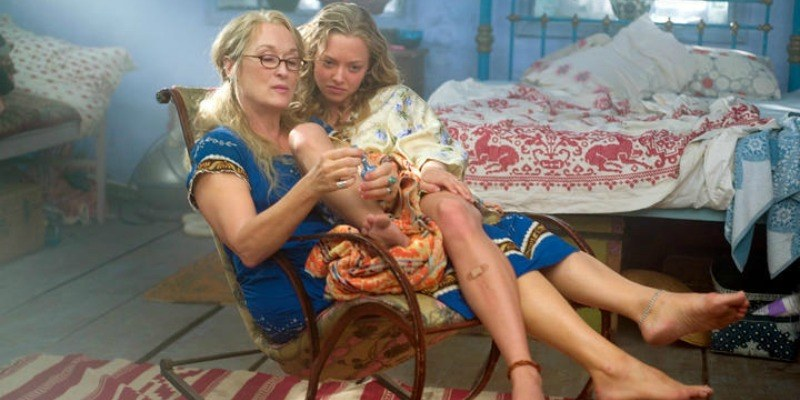 Amanda Seyfried is sitting in Meryl Streep's lap in Mamma Mia!