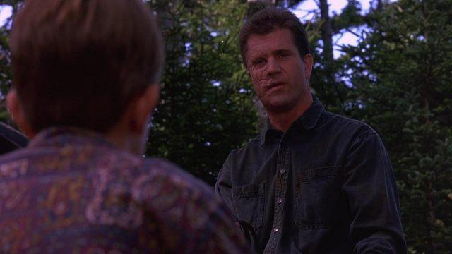 A disfigured Mel Gibson speaks to a small boy in a lightly wooded area
