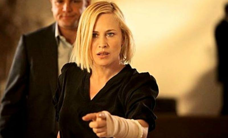 Patricia Arquette is in a black outfit and pointing.