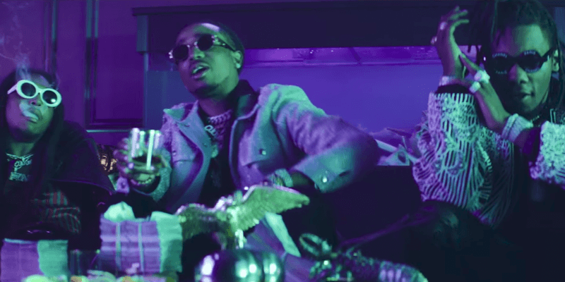 Members of group Migos are sitting down on a couch smoking and drinking in a club