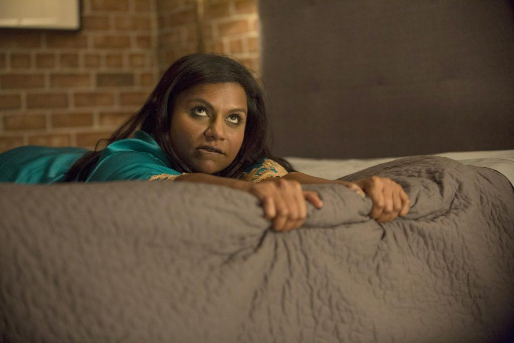 Mindy Lahiri lies on a bed gripping the side