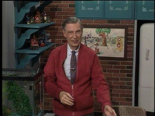 Fred Rogers next to a fish tank on set
