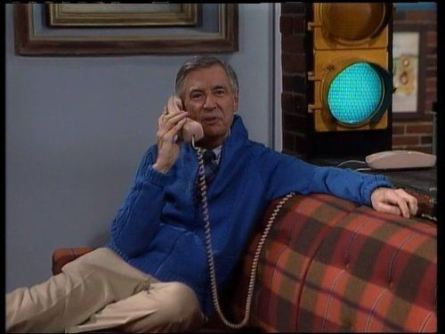 Fred Rogers sitting on a couch talking on the phone in front of a traffic light shining green