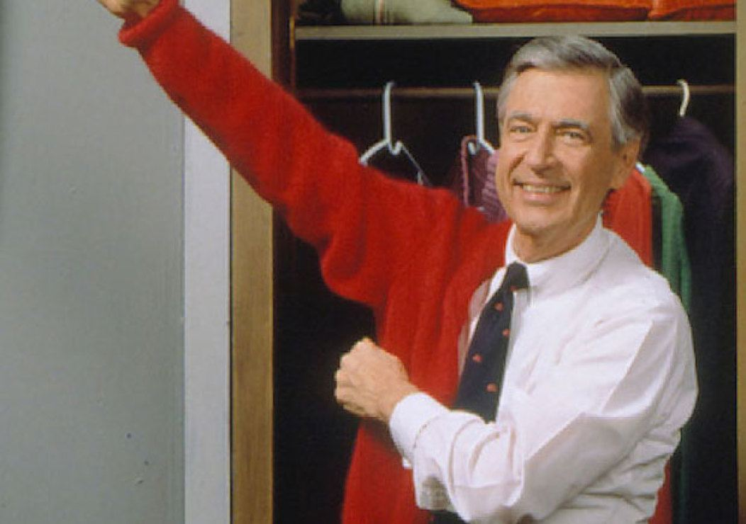 Fred Rogers standing in front of an open closet putting on a red sweater