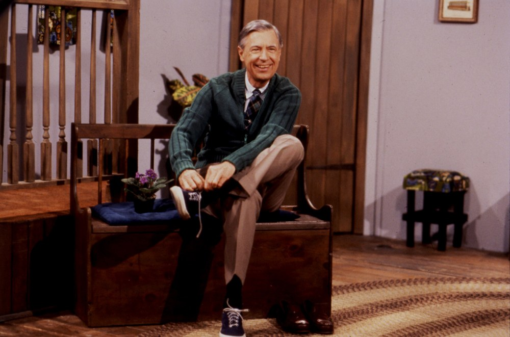 Fred Rogers sits on a bench on set taking off his shoes