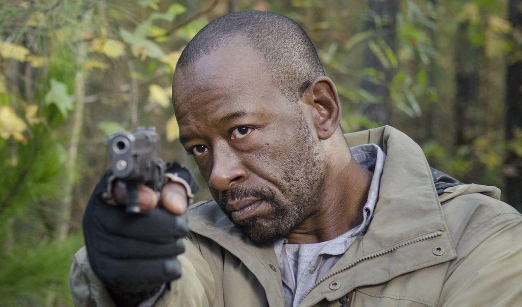 Morgan, wearing a tan jacket, and aiming a gun straight ahead of him with his right hand