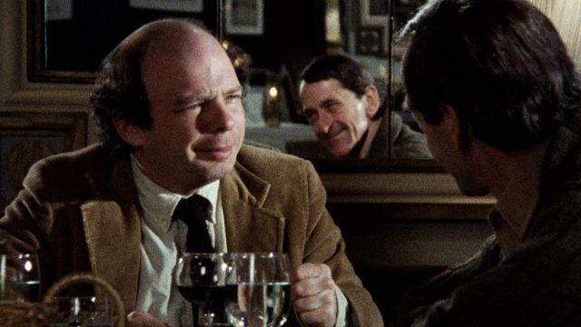Wally Shawn, sitting across from a man in a restaurant, as the two have a deep conversation