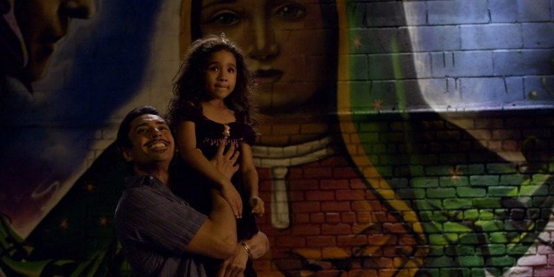 A father is holding up his little girl in front of a mural.