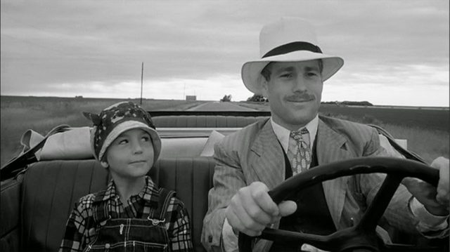 A man and a small boy driving together, as they smile pensively