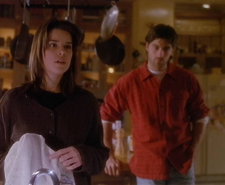 Julia doing dishes in the kitchen looking surprised as Charlie stands behind her