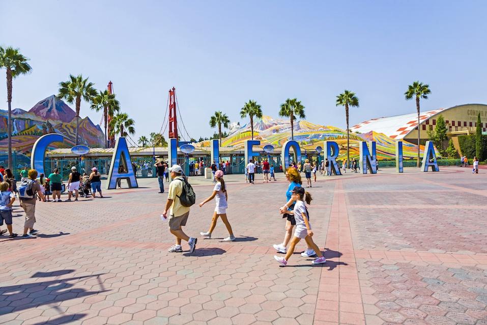 people visit Disneyland and walk over commemorative bricks with