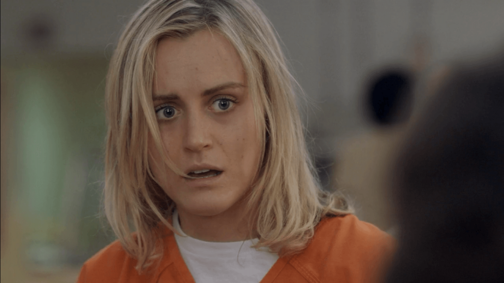 Piper, wearing an orange prison jumpsuit, and looking shocked off into the distance