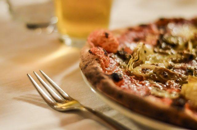 Pizza, beer and a fork seen on a table.