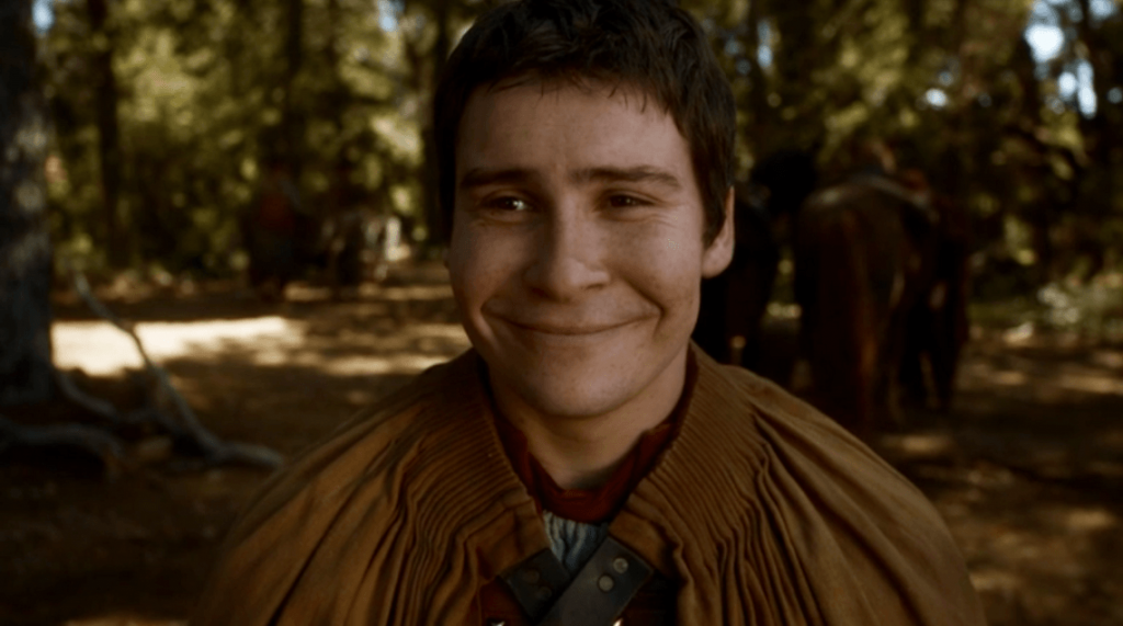 Podrick, wearing a simple brown tunic, and smiling widely into the camera