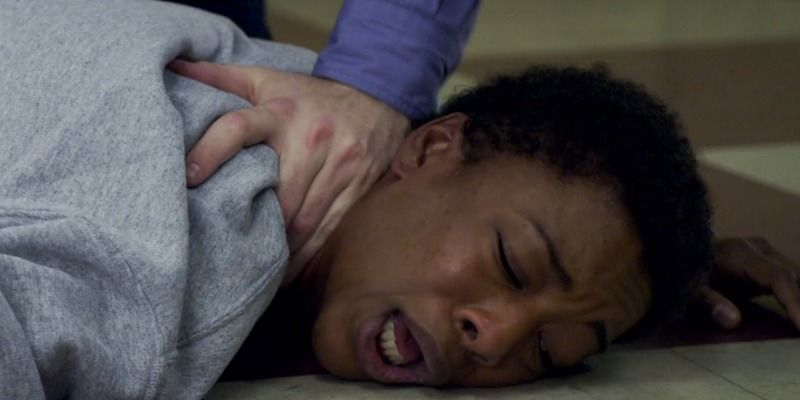 Poussey is being crushed on the ground under an officer.