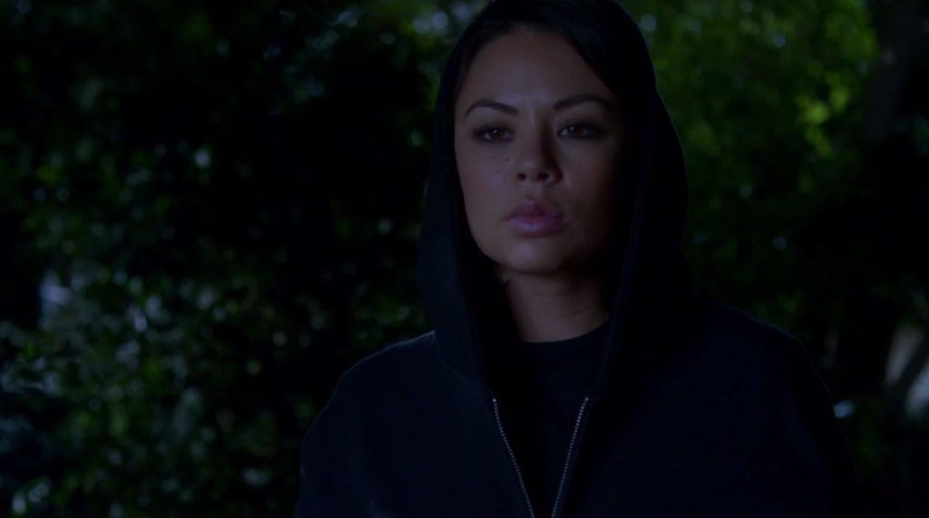 Mona in a black hoodie at night