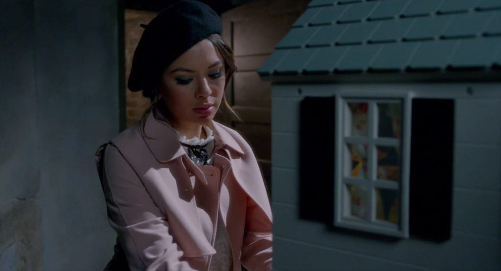 Mona wearing a beret and a pink jacket looking at a dollhouse