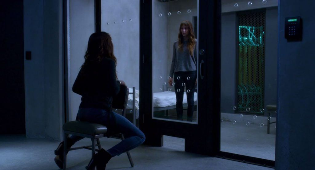 Spencer looks through a glass door at her twin sitting in a chair