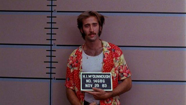 A young Nicolas Cage in Raising Arizona, in a mug shot wearing an orange floral button up shirt, opened over a white tank top