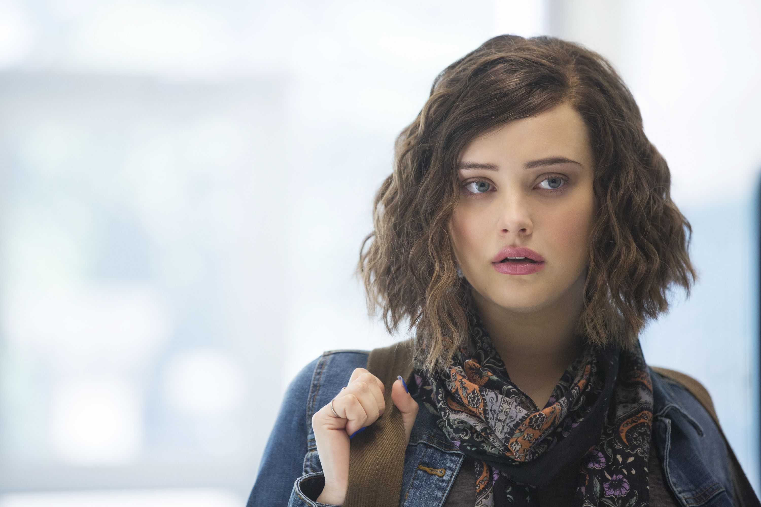 Hannah Baker holds onto the strap of her backpack while standing in a hallway