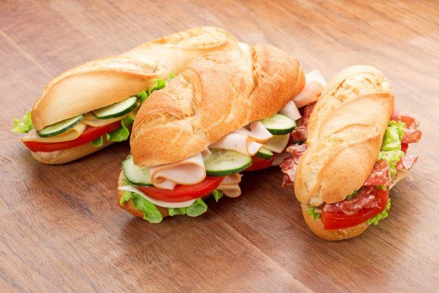 Sandwiches with savory fillings on wooden table.