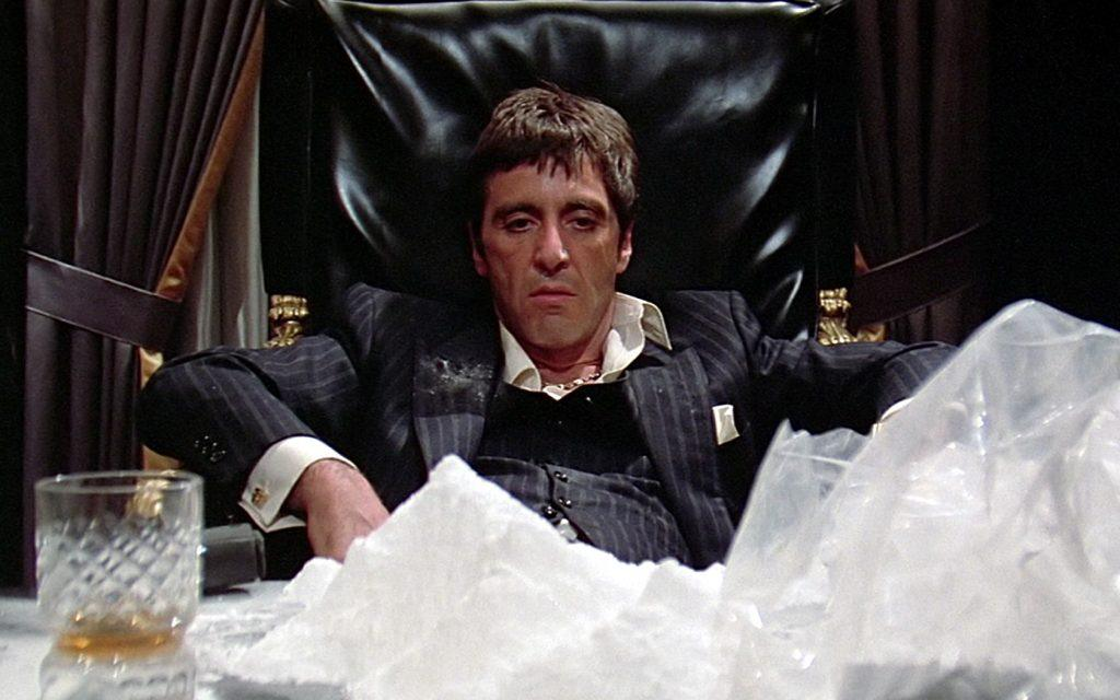 Al Pacino as Tony Montana, sitting in a large leather chair, in front of a mounds of cocaine