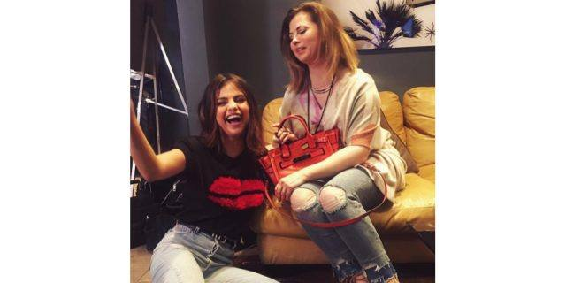 Selena Gomez sits on the ground, laughing, next to her mother, who is seated on a yellow leather couch and holding a Coach bag.