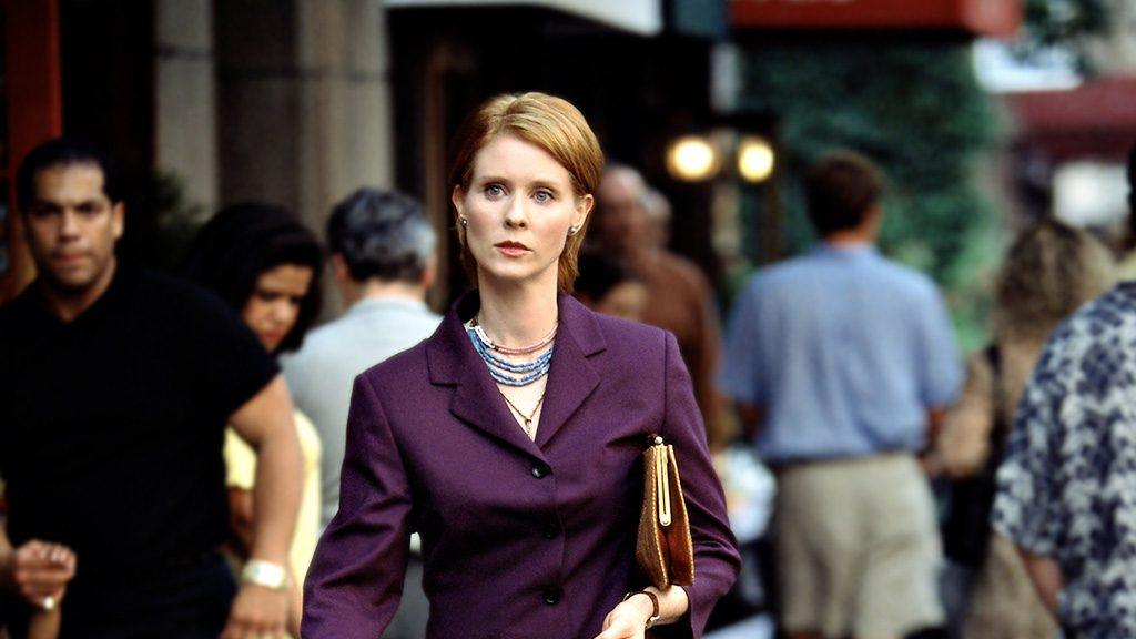 Miranda in a purple blazer with a purse under her arm walks through a crowd of people