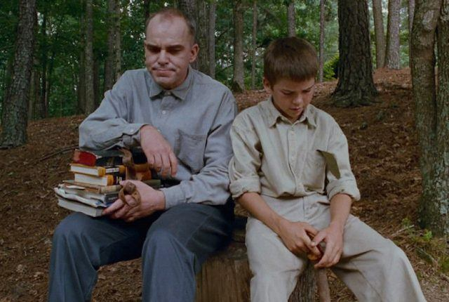 Billy Bob Thornton, sitting on a stump next a child, while resting his arm on a stack of books
