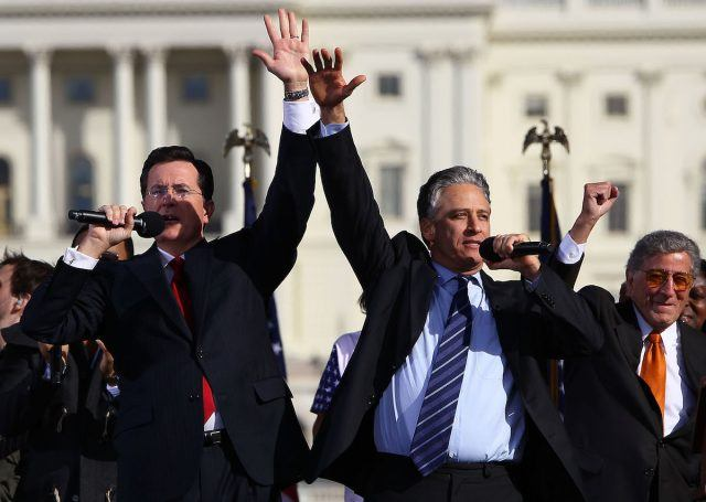 Stephen Colbert and Jon Stewart stand side-by-side, holding microphones and waving to the crowd, at their rally on the National Mall.