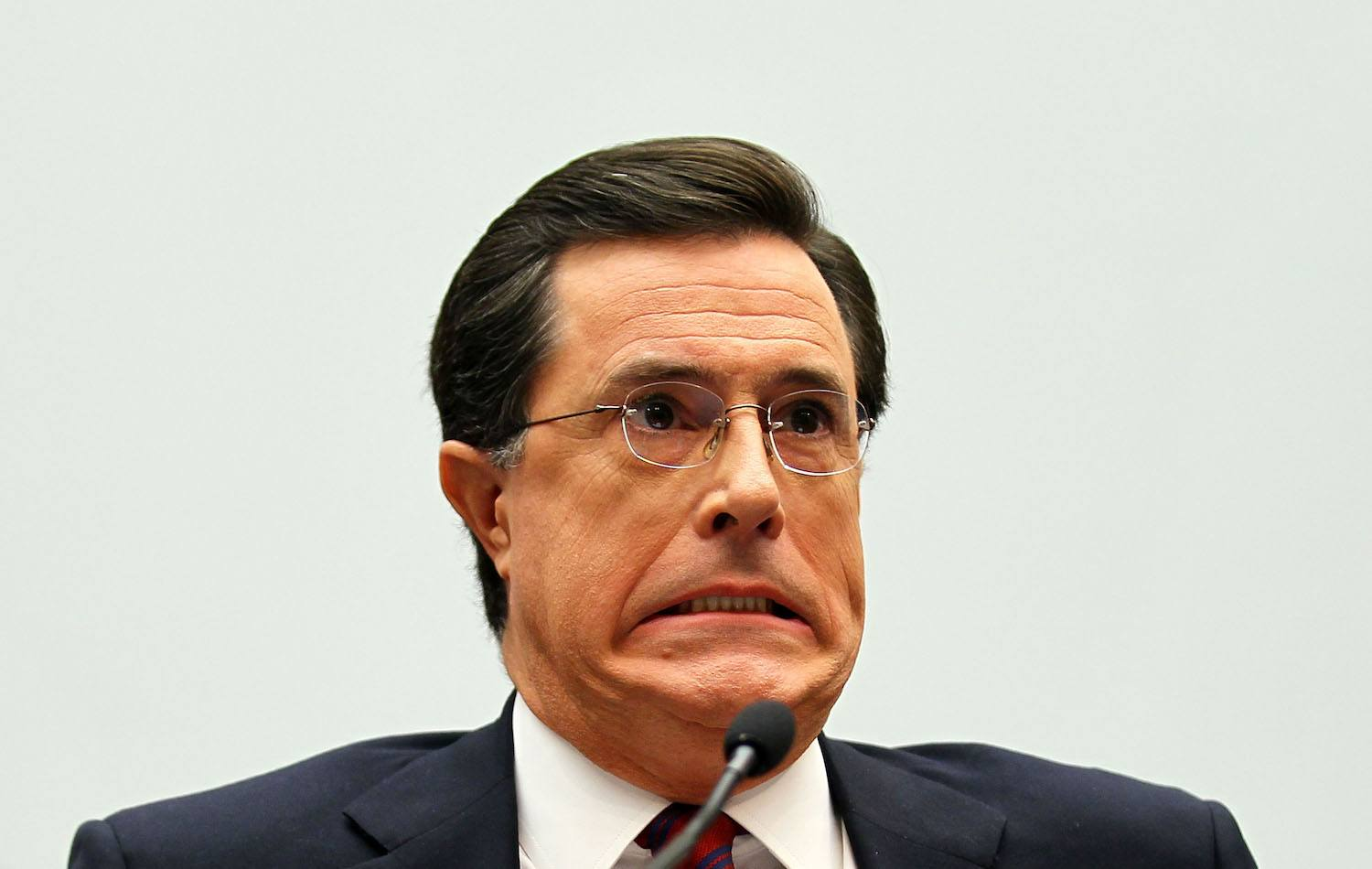Stephen Colbert makes a face while talking into a mic