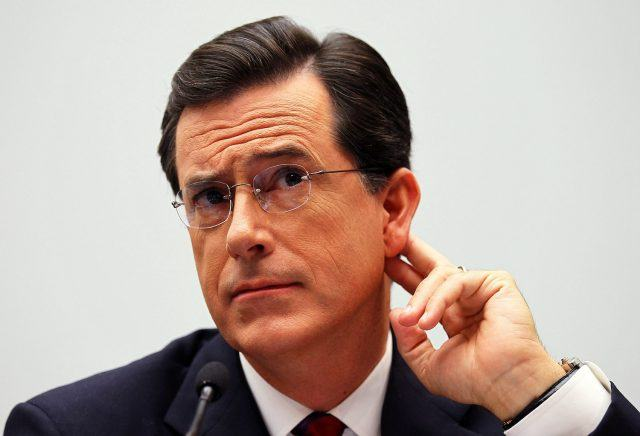 Stephen Colbert holds his ear like he's trying to hear what someone is saying to him.