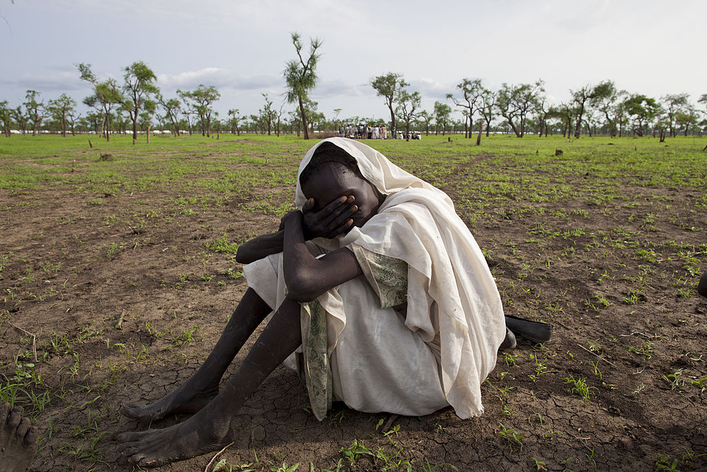 A Sudanese woman grieves near a Sudanese refugee camp