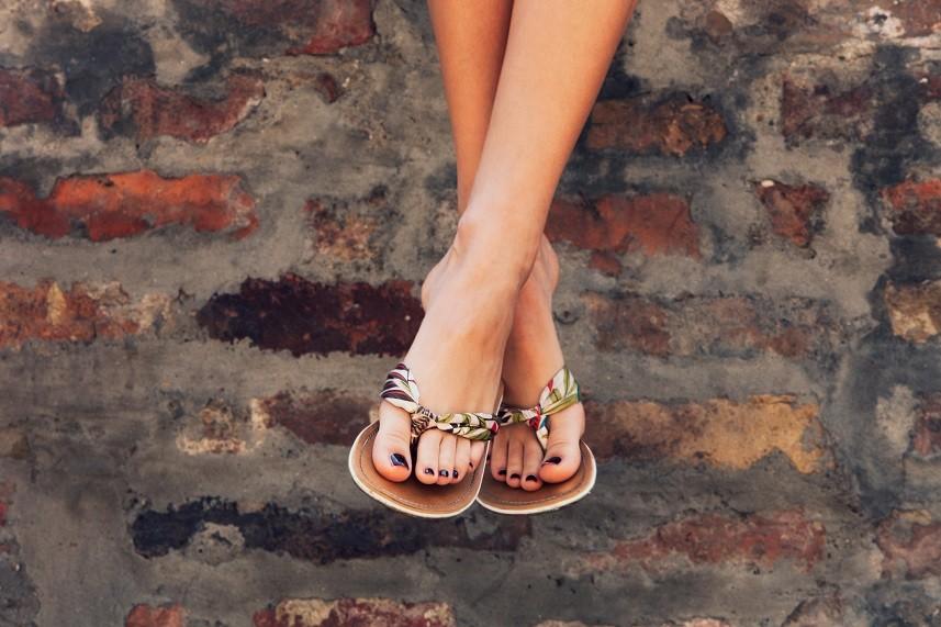 woman legs in summer flat slippers