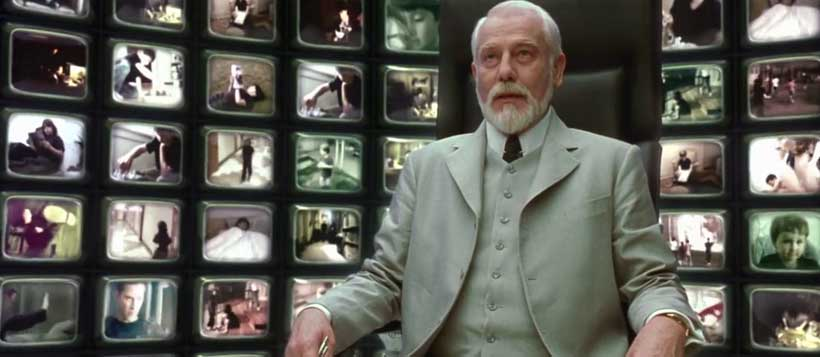 The Architect, wearing a white suit, sitting in front of a large bank of TVs playing in the background