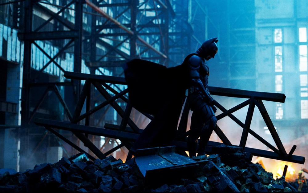 Batman, standing among rubble in the wake of an explosion