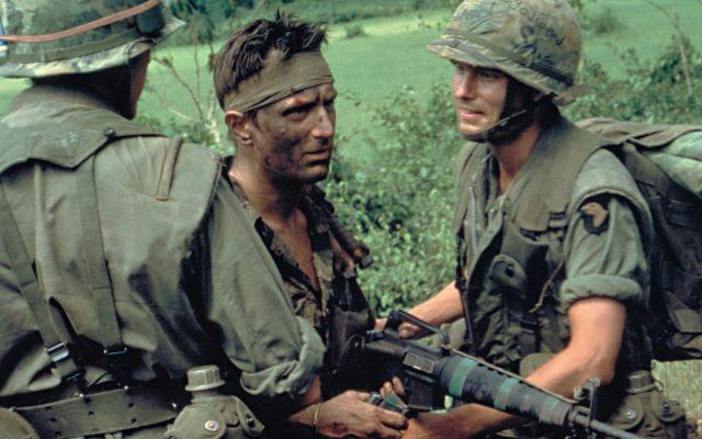 Three soldiers pose for a picture in the jungle of Vietnam, looking grimly into the camera