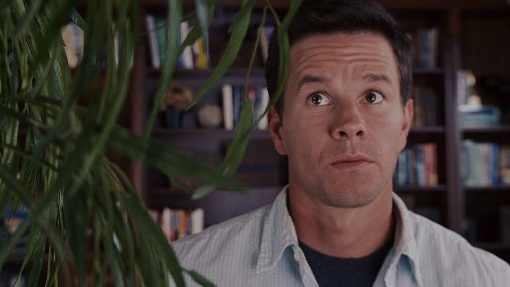 Mark Wahlberg looks up suspiciously at a plant
