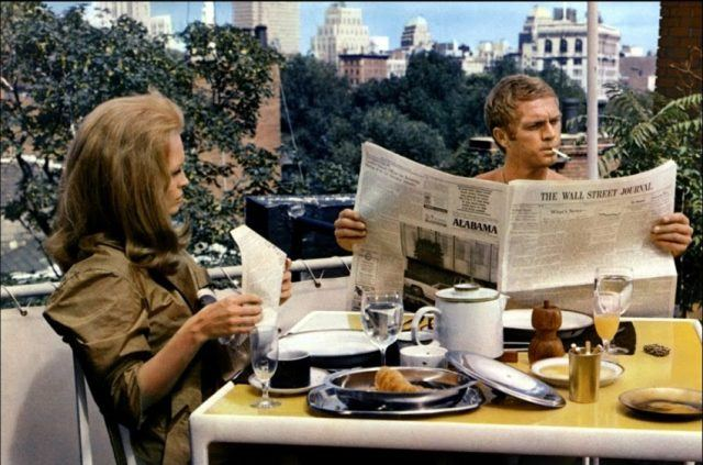 Steve McQueen sitting at a breakfast table reading a newspaper, while Faye Dunaway looks on