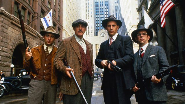 The cast of the Untouchables, posing in a city street and wielding various guns