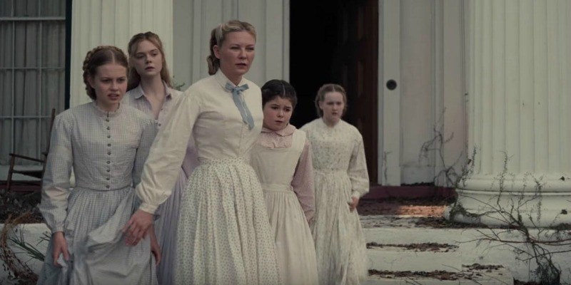 The female cast of The Beguiled stand outside of a house in white dresses.