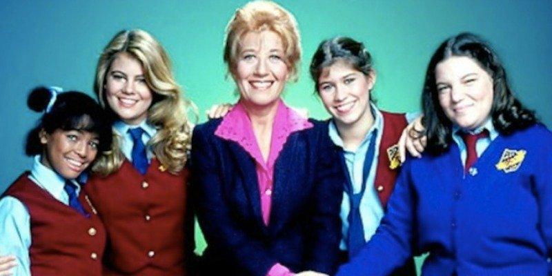 The cast of The Facts of Life are posing together in front of a green background.