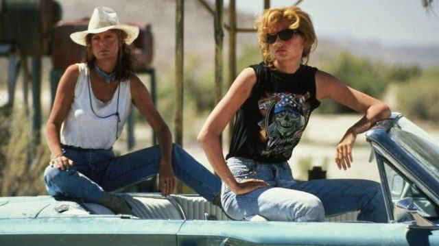 Geena Davis and Susan Sarandon, sitting on top of the seats in a blue convertible