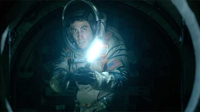 Jake Gyllenhaal holds up a flashlight in Life