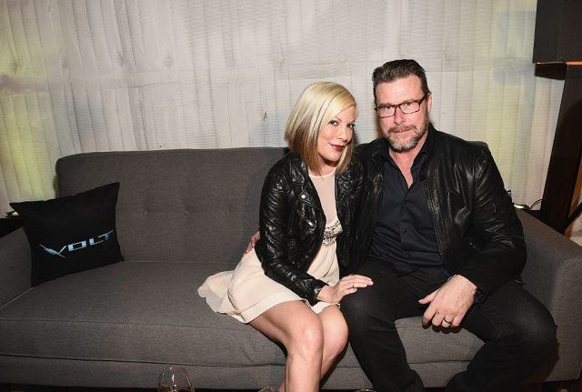 Tori Spelling and Dean McDermott sit on a grey couch together.