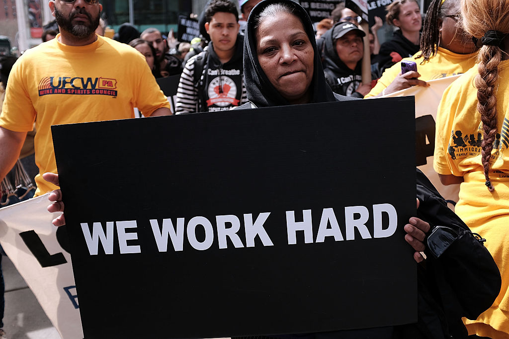 """group of demonstrators with sign that says """"we work hard"""""""