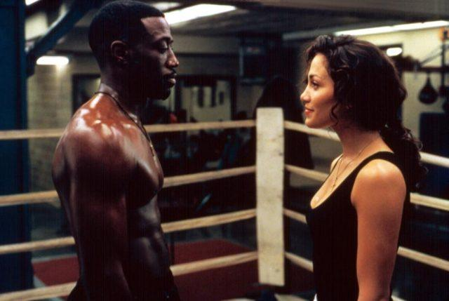 Wesley Snipes stands, shirtless, opposite Jennifer Lopez inside of a boxing ring in a scene from 'Money Train.'