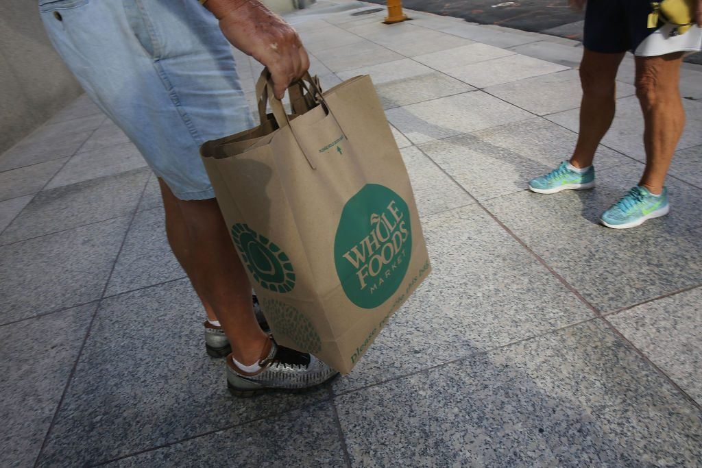 A customer with a Whole Foods Market shopping bag