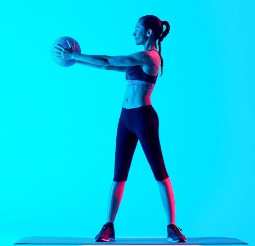 Woman exercising with Medicine Ball on blue background